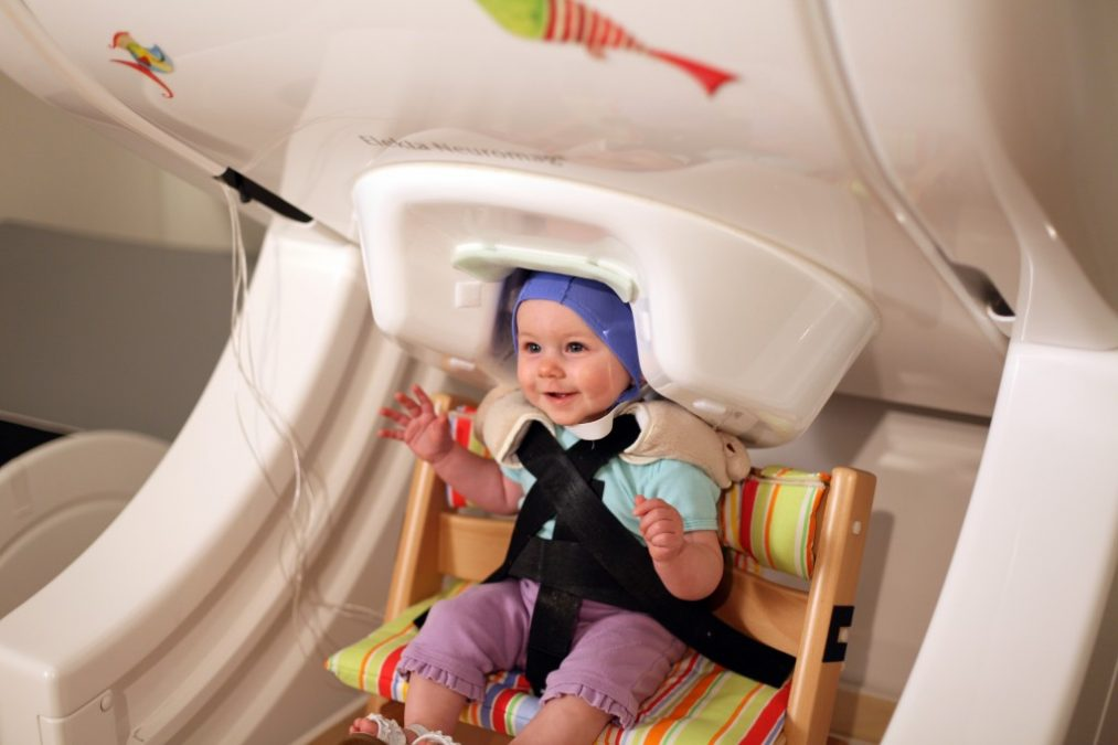 "A year-old baby sits in a brain scanner, called magnetoencephalography — a noninvasive and safe approach to measuring infant brain activity. The baby listens to speech sounds like ""da"" and ""ta"" played over headphones while researchers record her brain responses.  Credit:  Institute for Learning & Brain Sciences, UW."
