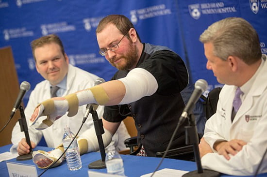 Will Lautzenheiser's (center) arms were amputated in 2011 — along with both legs — in a frantic attempt to save his life after a rampaging bacterial infection shut down his organs and killed the tissue in his limbs. Last month, Lautzenheiser received a bilateral arm transplant with the help of Simon Talbot (left), director of the Brigham's Upper Extremity Transplant Program, and Matthew Carty (right), head of the Brigham's Lower Extremity Transplant Program.  Credit:  Kris Snibbe/Harvard Staff Photographer.