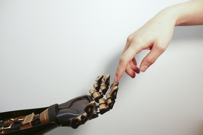 Human finger touches robotic finger. The transparent plastic and black device on the golden